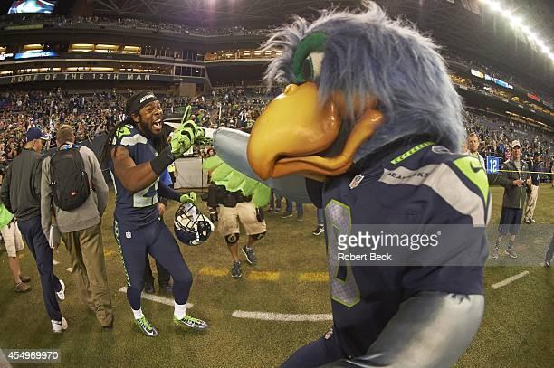 Seattle Seahawks Richard Sherman with mascot Blitz after winning game vs Green Bay Packers at CenturyLink Field Seattle WA CREDIT Robert Beck