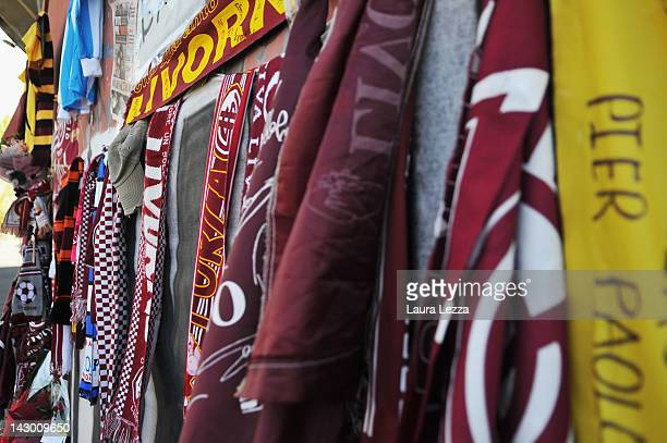 A football shirt from rival club AC Pisa 1909 hangs on a wall amongst scarves graffiti and floral tributes outside Armando Picchi Stadium where the...
