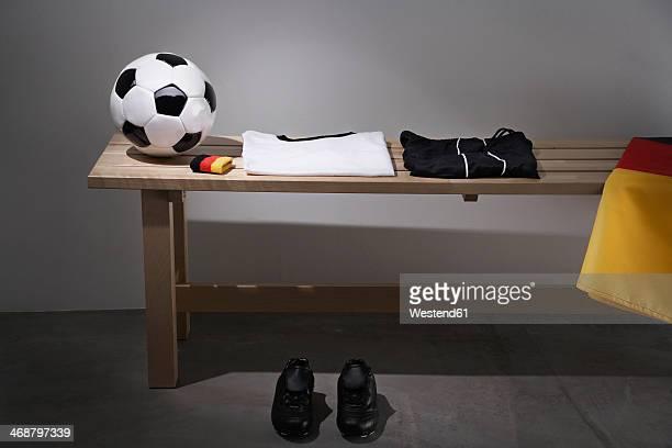Football shirt, pants and shoes on bench with German flag, studio shot