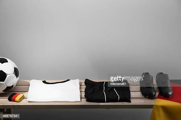 Football shirt, pants and shoes on bench with German flag, studio shot