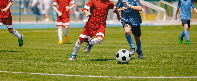 Football Soccer Players Running with Ball. Footballers Kicking Football Match. Young Soccer Players Running After the Ball. Kids in Soccer Red and Blue Uniforms. Soccer Stadium in the Background 1149107191