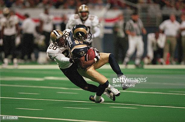 Football St Louis Rams Isaac Bruce in action during tackle vs New Orleans Saints Jay Bellamy St Louis MO
