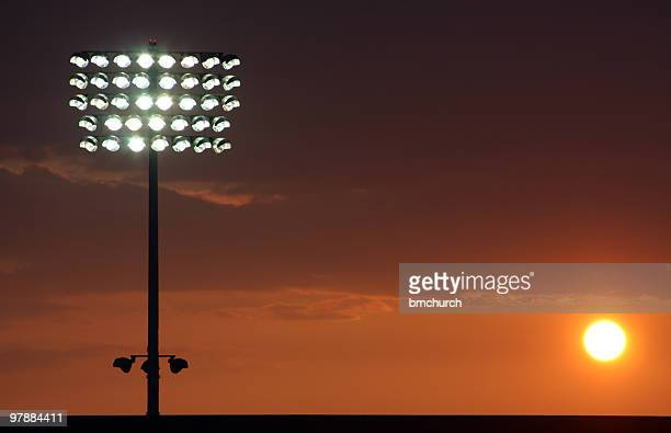 football stadium lights at sunset - stadium lights stock photos and pictures