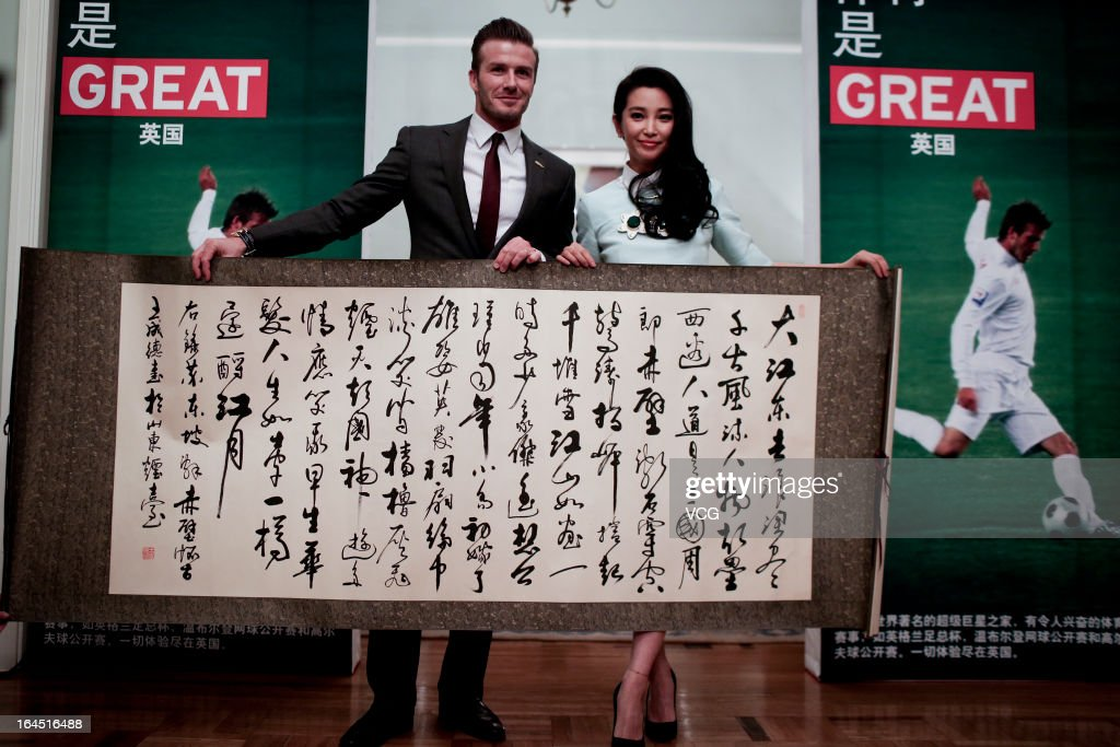 Football star David Beckham recevies a gift from Chinese actress Li Bingbing at the British Embassy on March 24, 2013 in Beijing, China.