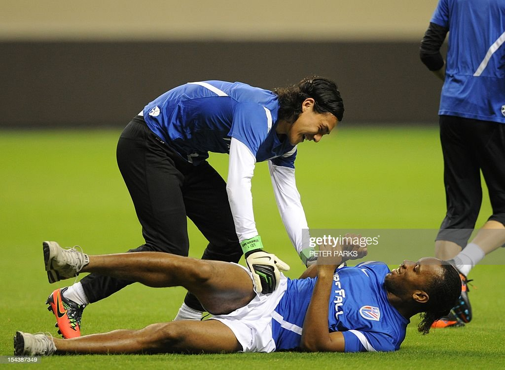 Football star Didier Drogba (bottom) is jumped on by Shanghai Shenhua goalkeeper Dong Guangxiang (C) before a training session at Hongkou stadium in Shanghai on October 19, 2012. Drogba has injured his right ankle so he will not play the next match for his Chinese club after returning from international duty and into a row that has seen his teammates reportedly refusing to practise over unpaid wages. AFP PHOTO/Peter PARKS