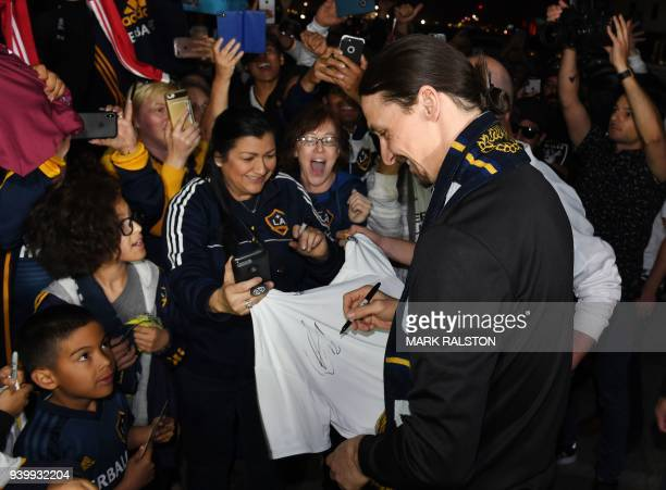 TOPSHOT Football star Zlatan Ibrahimovic is greeted by fans after arriving at Los Angeles International Airport to begin his new contract with local...