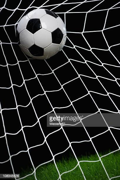 Football striking on net, close up