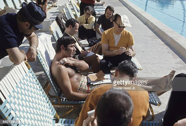 Casual portrait of New York Jets QB Joe Namath sitting on pool chair surrounded by media before Super Bowl III vs Baltimore Colts. Fort Lauderdale,...