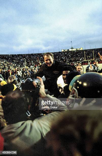 Super Bowl IX Pittsburgh Steelers head coach Chuck Noll victorious getting carried off the field by Franco Harris and Mean Joe Green after winning...
