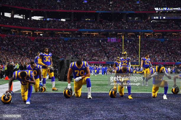 Super Bowl LIII Los Angeles Rams players down on one knee in endzone during prayer before game vs New England Patriots at MercedesBenz Stadium...