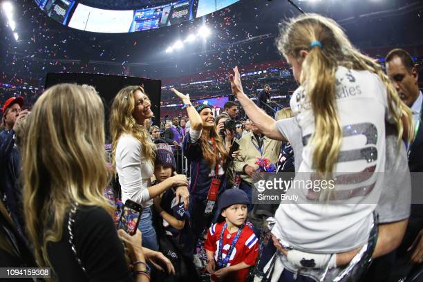 Super Bowl LIII New England Patriots QB Tom Brady victorious holding his daughter Vivian and giving high five to sister Julie with wife Gisele...