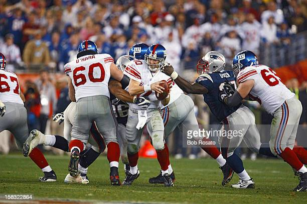 Super Bowl XLII New York Giants QB Eli Manning in action under pressure and breaking free from New England Patriots Jarvis Green at University of...