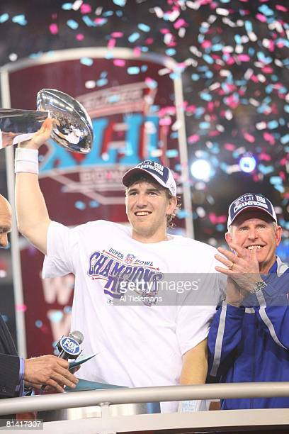 Football Super Bowl XLII New York Giants QB Eli Manning victorious holding Vince Lombardi trophy during celebration with coach Tom Coughlin after...