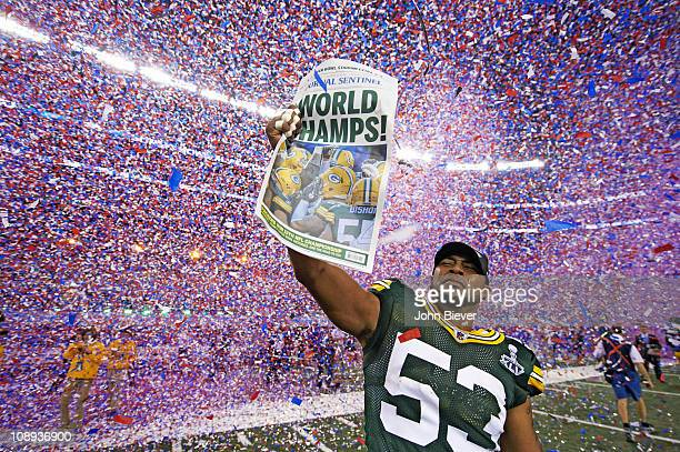 Super Bowl XLV Green Bay Packers Diyral Briggs victorious holding Milwaukee Journal Sentinel newspaper during celebration after winning game vs...