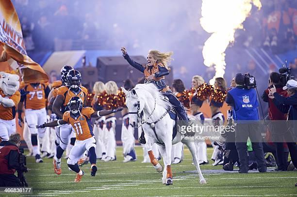 Super Bowl XLVIII: Ann Judge-Wegener riding on Denver Broncos mascot Thunder, leading team onto field before game vs Seattle Seahawks at MetLife...