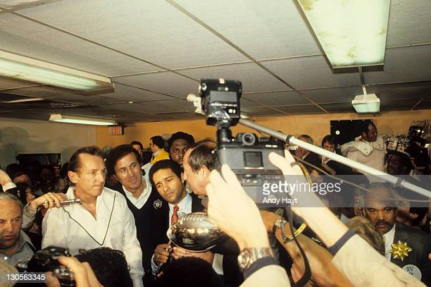 Super Bowl XV Oakland Raiders general manager Al Davis about to receive Lombardi trophy from NFL commissioner Pete Rozelle in locker room after...