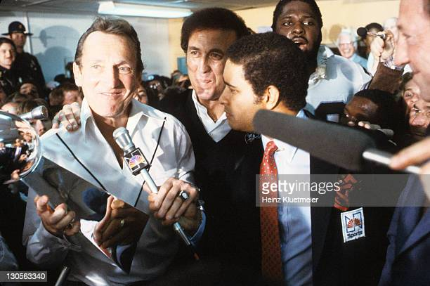 Super Bowl XV Oakland Raiders general manager Al Davis victorious in locker room holding Lombardi trophy during interview with NBC Sports announcer...