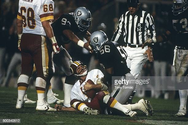 Super Bowl XVIII Washington Redskins QB Joe Theismann down on field looking up after getting sacked by Los Angeles Raiders Jeff Barnes during game at...
