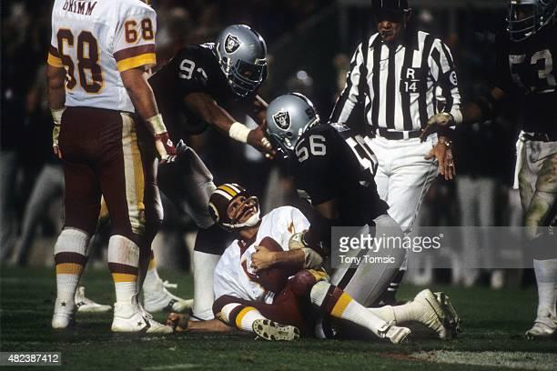 Super Bowl XVIII Washington Redskins QB Joe Theismann lying down on field after sack by Los Angeles Raiders Jeff Barnes at Tampa Stadium Tampa FL...