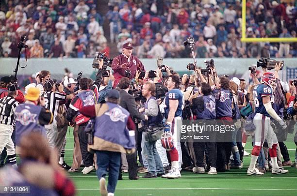 Football Super Bowl XXVI Washington Redskins coach Joe Gibbs victorious getting carried off field by team after winning game vs Buffalo Bills View of...