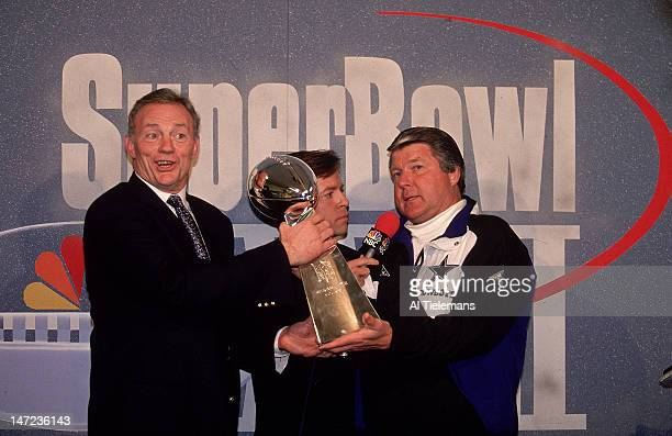 Super Bowl XXVII Dallas Cowboys owner Jerry Jones victorious with Vince Lombardi Trophy NBC Sports announcer Bob Costas and head coach Jimmy Johnson...