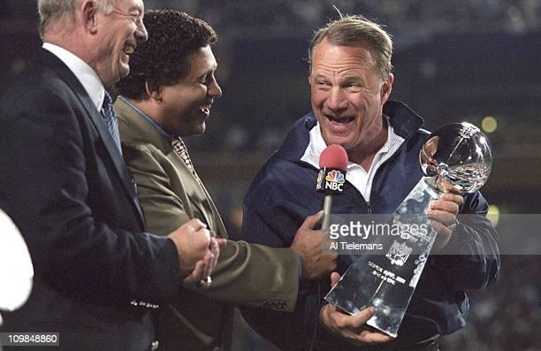 Super Bowl XXX Dallas Cowboys coach Barry Switzer victorious holding Vince Lombardi Trophy with NBC Sports announcer Greg Gumbel and Cowboys owner...