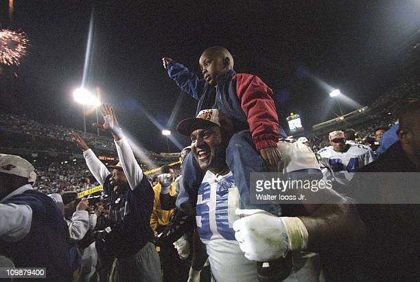 Super Bowl XXX Dallas Cowboys Derek Kennard victorious carrying son Devon on shoulders after winning game vs Pittsburgh Steelers at Sun Devil...
