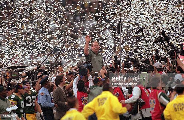 Football Super Bowl XXXI Green Bay Packers coach Mike Holmgren victorious getting carried off field by Reggie White with media and confetti after...