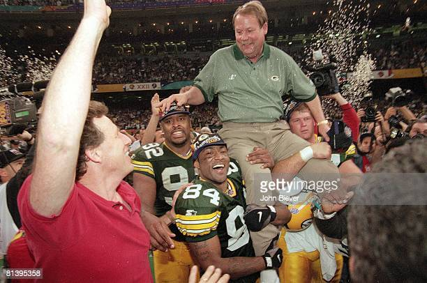 Football Super Bowl XXXI Green Bay Packers coach Mike Holmgren victorious getting carried off field by Reggie White and Andre Rison team after...
