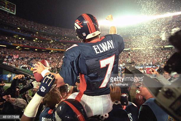 Super Bowl XXXII Rear view of Denver Broncos QB John Elway victorious after winning game vs Green Bay Packers at Qualcomm Stadium Elway being carried...