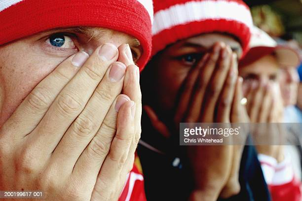 Football supporters at match, hands over mouths, close-up