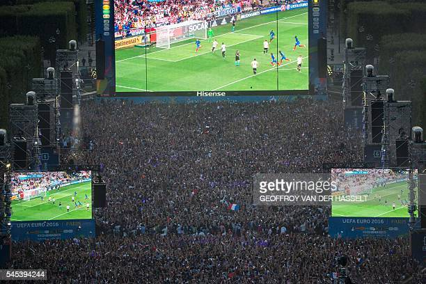 Football supporters celebrate as they watch the Euro 2016 semifinal football match between Germany and France at the Paris Champs de Mars Fan Zone on...
