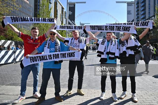 """Football supporters hold scarves reading """"Football is for the Fans"""", in response to the European Super League , as they arrive at Wembley Stadium to..."""