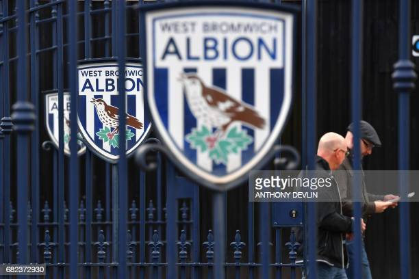 Football supporters walk past the West Bromwich Albion logo before the English Premier League match between West Bromwich Albion and Chelsea at The...