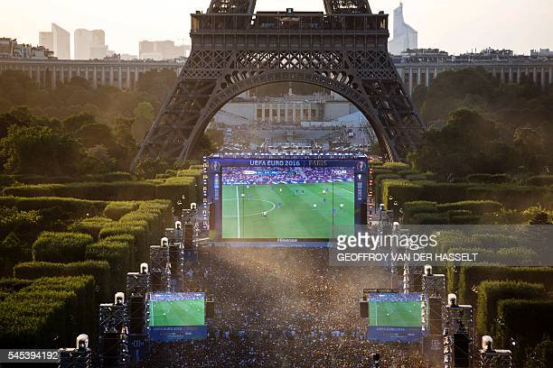 Football supporters watch the Euro 2016 semifinal football match between Germany and France at the Paris Champs de Mars Fan Zone next to the Eiffel...