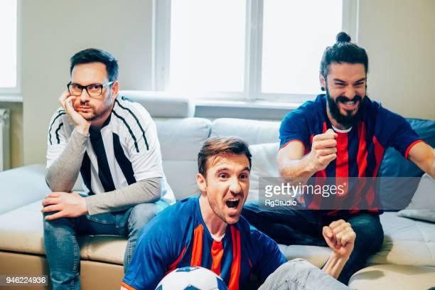fußball-fans, die gerade ein spiel im fernsehen zu hause - the championship football league stock-fotos und bilder