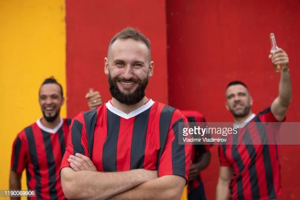 fußball-team-kapitän stehenarme arme auf farbigem hintergrund gekreuzt - mannschaftskapitän stock-fotos und bilder