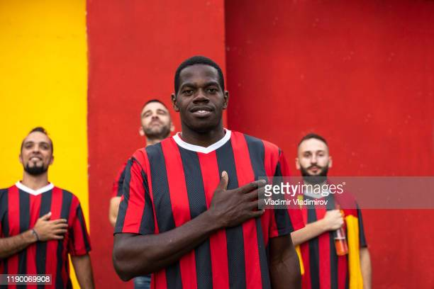 football team captain standing hand on heart on color background - team captain stock pictures, royalty-free photos & images