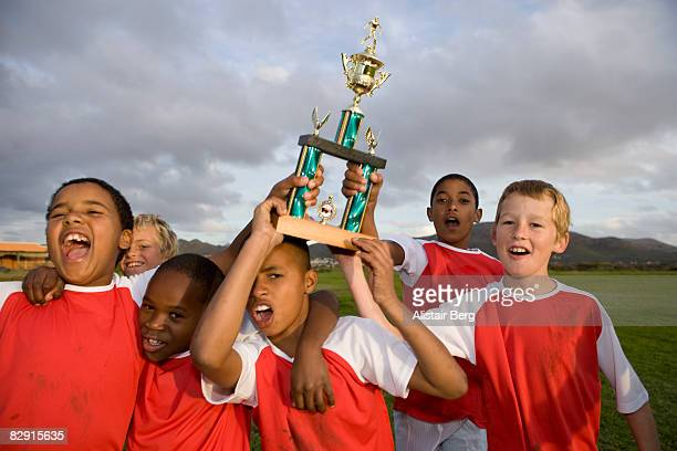 Football team celebrating with trophy