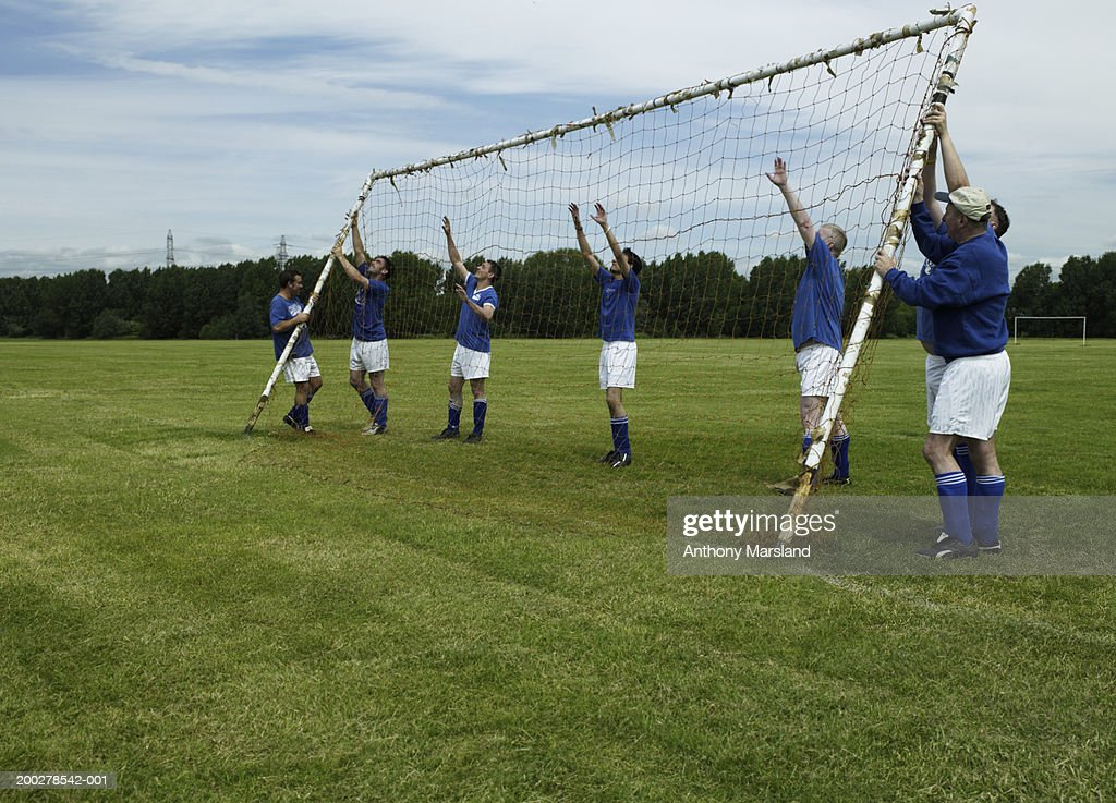 Football team erecting goal on pitch : Stock Photo