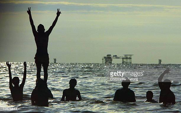 Football team from an oil refinery in Seria take a celebratory bath in the South China Sea after beating a rival refinery team on the beach in the...
