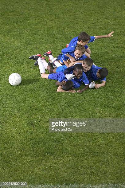 Football team of boys (8-12) in pile on ground, smiling