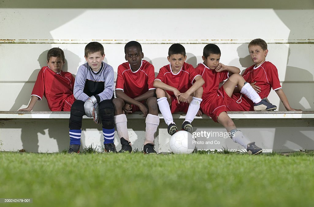 Football team of boys (8-12) sitting on bench, portrait : Stock Photo