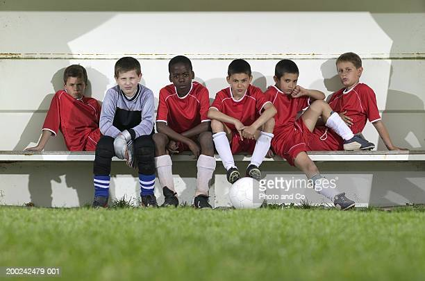 football team of boys (8-12) sitting on bench, portrait - reserve athlete stock pictures, royalty-free photos & images