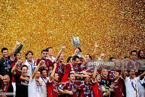 Football team players of AC Milan celebrate with the trophy after winning the Italian Super Cup 2011 match against Inter Milan at China's National...