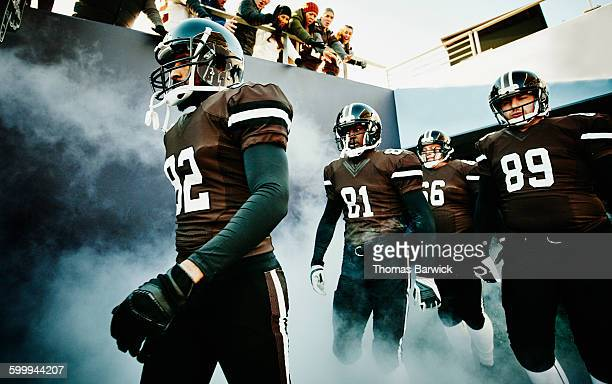 football team walking out of stadium tunnel - amerikanischer football stock-fotos und bilder