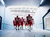 Football team walking out to crowded stadium