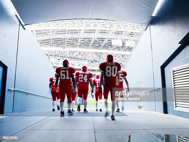 football team walking out to crowded stadium - スポーツユニフォーム ストックフォトと画像