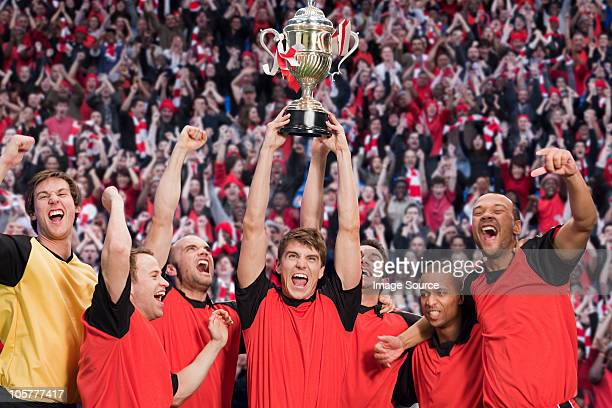football team winning a trophy - cup stock pictures, royalty-free photos & images