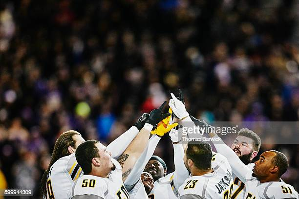 football team with arms raised after win - american football sport stock pictures, royalty-free photos & images